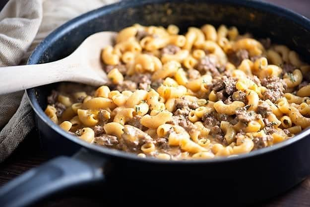 Wooden spoon in a skillet of macaroni noodles and hamburger.