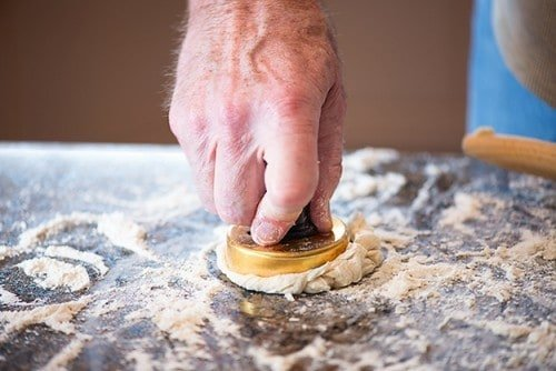 man cutting biscuit dough with biscuit cutter.