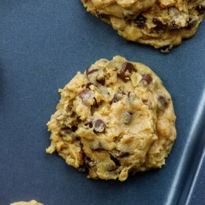 Close up shot of cookie dough spread out on a baking sheet.