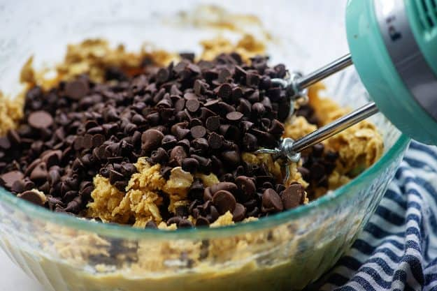 chocolate chips over cookie dough in glass mixing  bowl