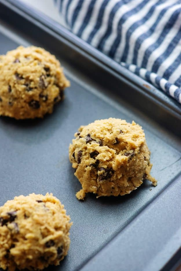 cookie dough on baking sheet with blue striped napkin