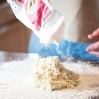 man sprinkling flour over biscuit dough.