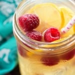 A clear glass jar with fruits and a polka dot straw in it.
