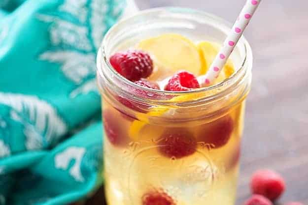 A glass jar with raspberries and lemons floating in a drink.