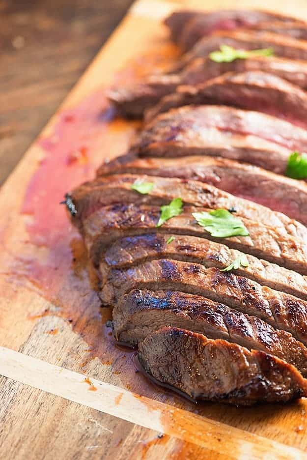 A cut flank steak on a wooden cutting board.