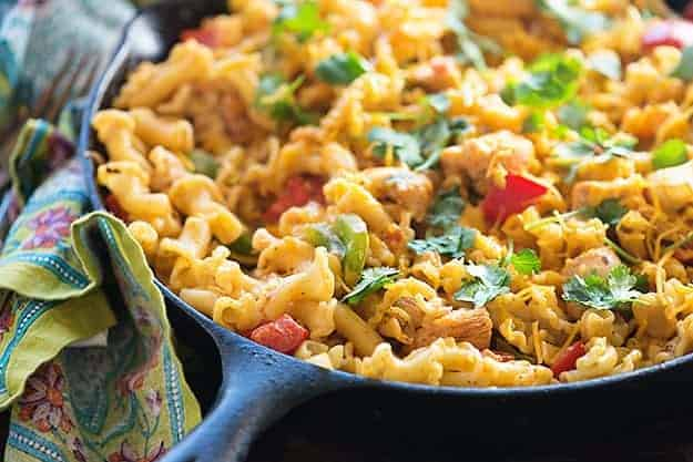 A cast-iron skillet cooking pasta with chicken in it.
