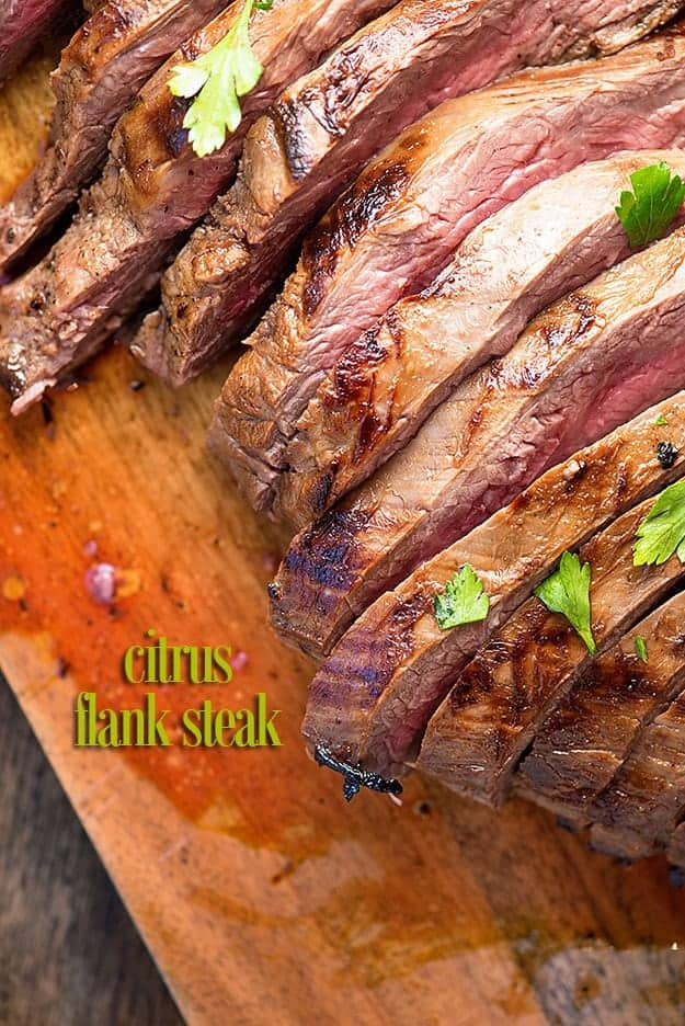 A filleted flank steak on a wooden cutting board.