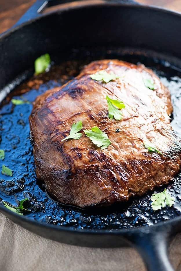 Flank steak in a cast-iron skillet.