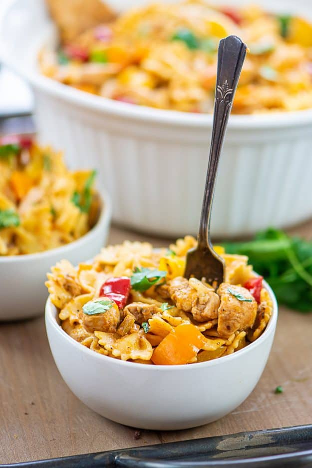 pasta with chunks of chicken and vegetables in white bowl with vintage fork.