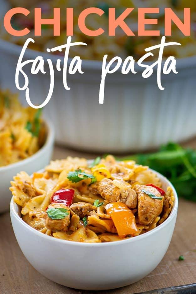 chicken fajita pasta on wooden board for Pinterest.