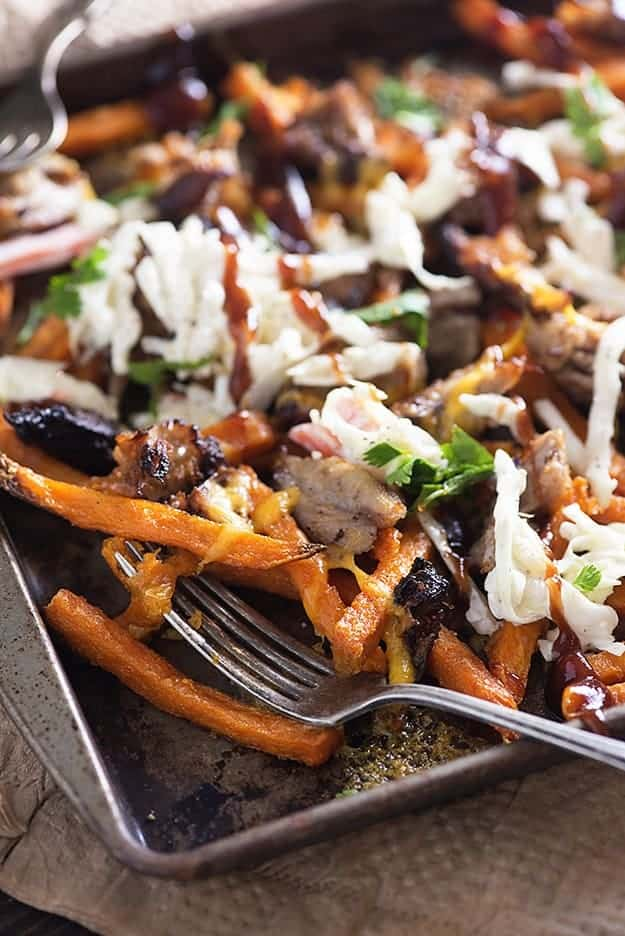 A close up of a baking sheet of loaded sweet potato fries.