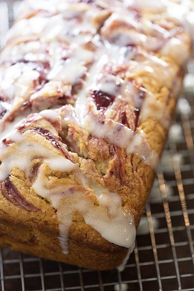 A close up of raspberry muffin bread topped with white icing.