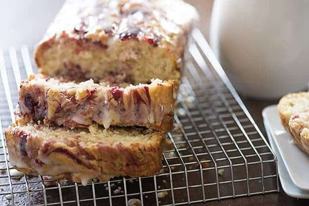 A sliced loaf of raspberry bread loaf on a wire cooling rack.
