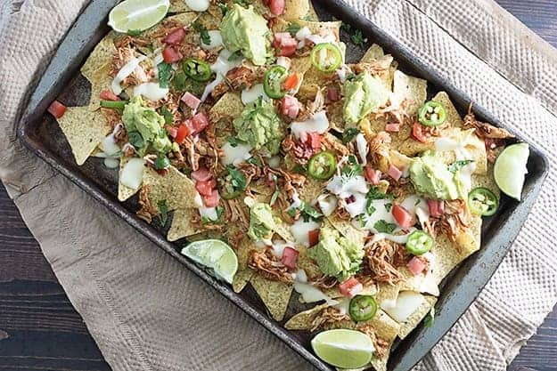 These sheet pan nachos use my favorite slow cooker taco chicken for a quick weeknight meal!