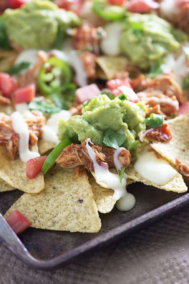 These sheet pan nachos are topped with slow cooker shredded chicken and the easiest white queso you'll ever make!