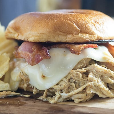 Honey mustard chicken made in the Crock-Pot® slow cooker! The chicken is so flavorful and tender! I love these sandwiches topped with bacon and swiss cheese!