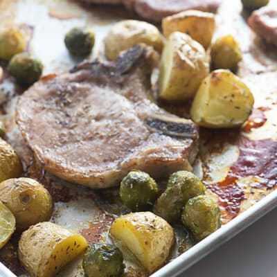 Pork chops, potatoes, and Brussel sprouts on a baking sheet.