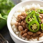 A cup of rice and beans topped with jalapenos.