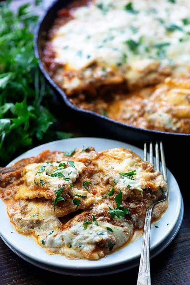 Lasagna and a fork on a white plate next to a cast-iron skillet.