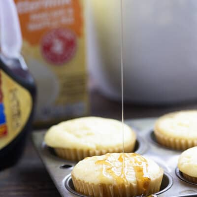 Syrup being drizzled on top of a pancake muffin.