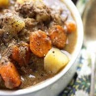 A cup of beef stew with carrots and potatoes.
