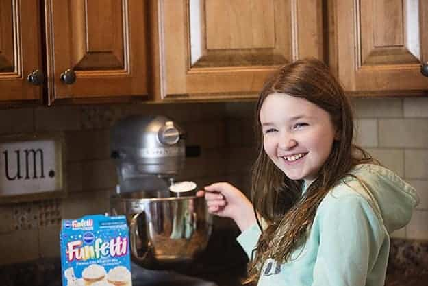 A girl adding ingredients to a stand mixer.