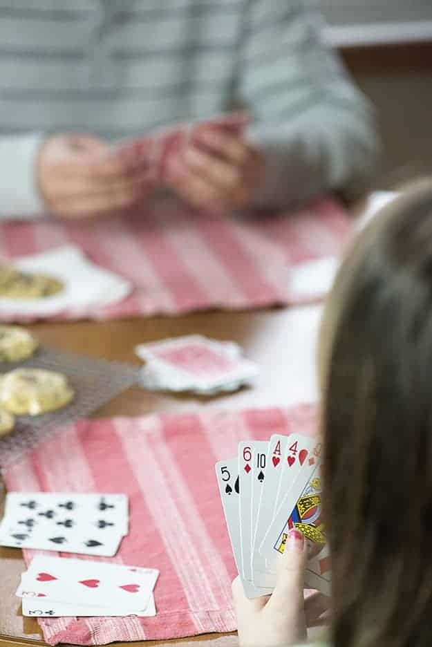 A girl playing cards at a table.