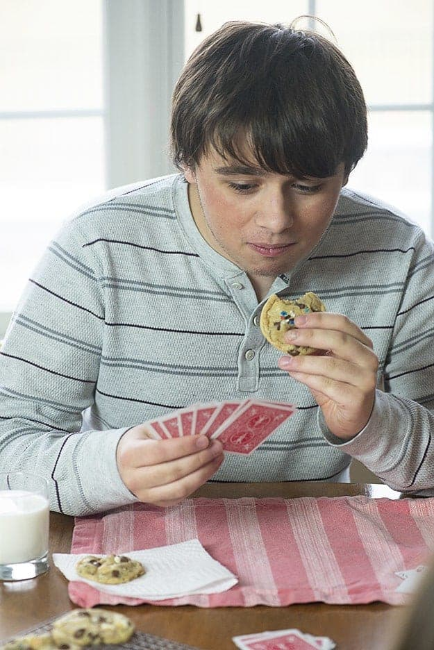 A boy eating a cookie white playing cards.
