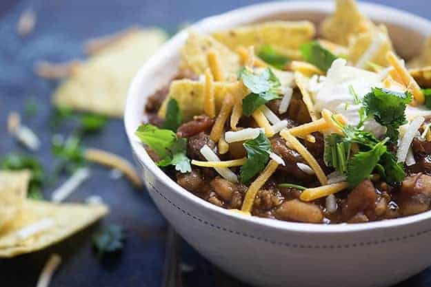 A bowl of chili topped with tortillas and shredded cheese.