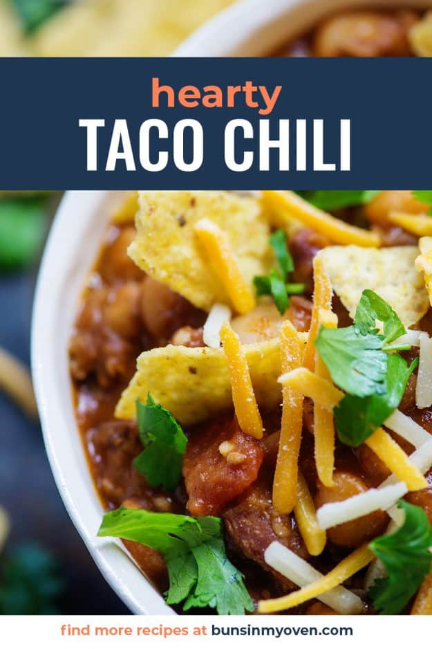taco chili in white bowl topped with chips and cheese.