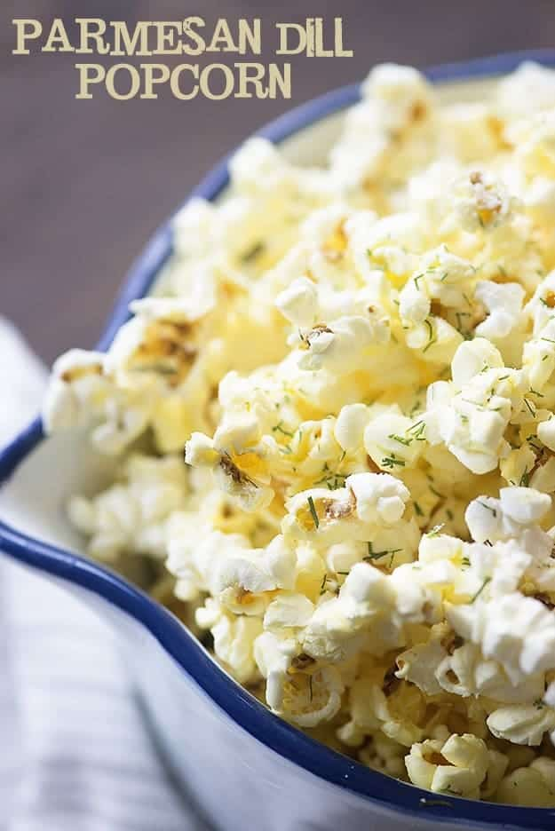 Popcorn topped with dill in a white bowl.