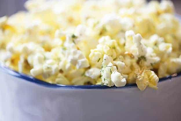 A close up of a white bowl of popcorn.