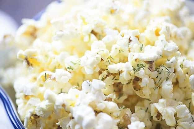 A close up of a bowl of popcorn topped with dill and parmesan.