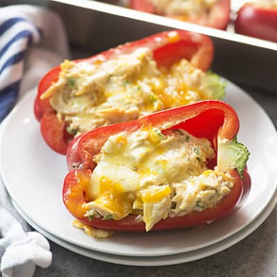 Stuffed red peppers on a white plate.