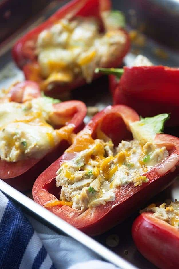 A close up of stuffed red peppers on a baking sheet.