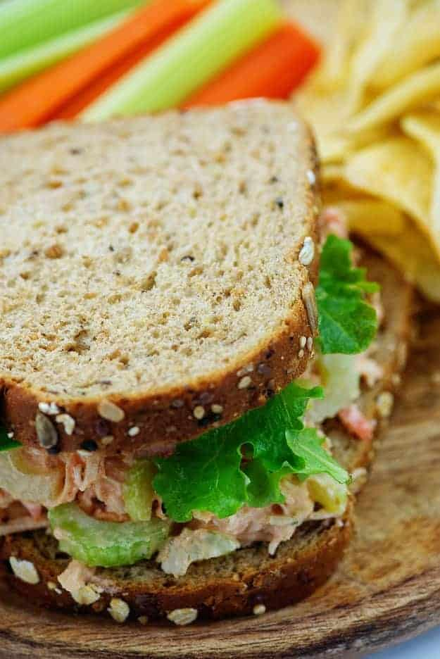 spicy chicken salad sandwich on wheat bread with chips on wooden board