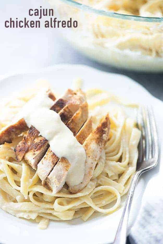 Sliced chicken on top of noodles on a white plate.