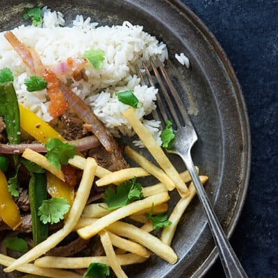 A plate of various vegetables, french fries, and rice.