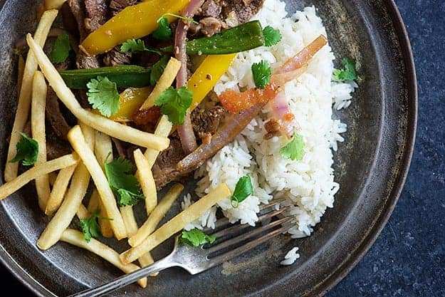 Authentic Peruvian lomo saltado - a steak stirfry served with rice and hot French fries!