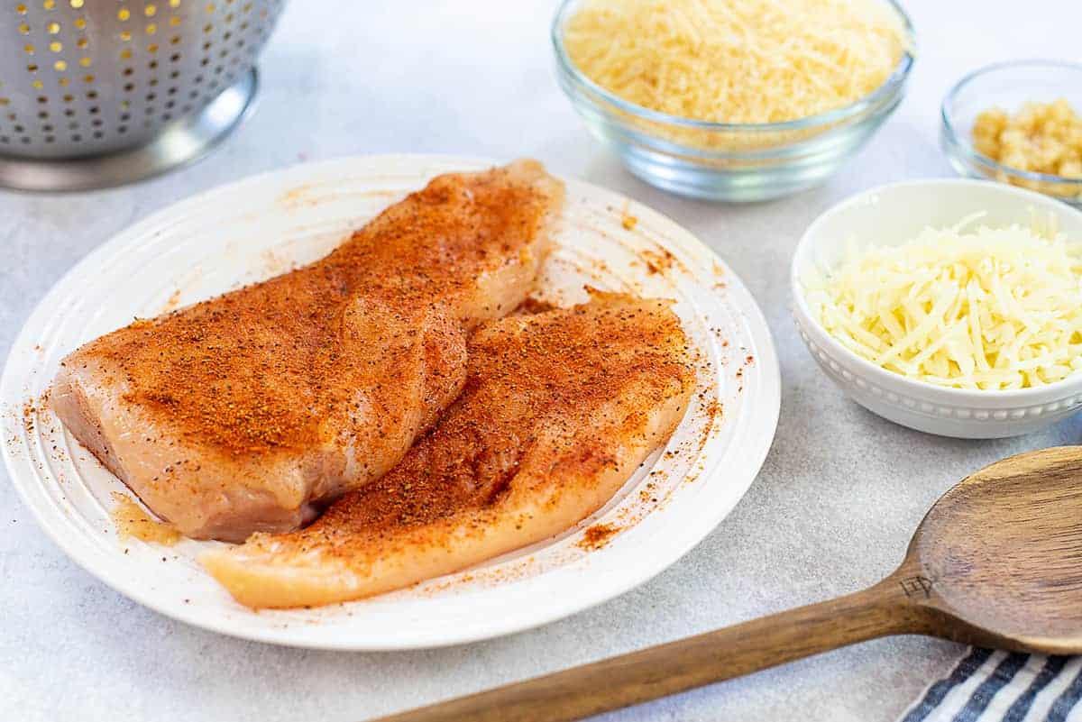 seasoned chicken breasts on white plate.
