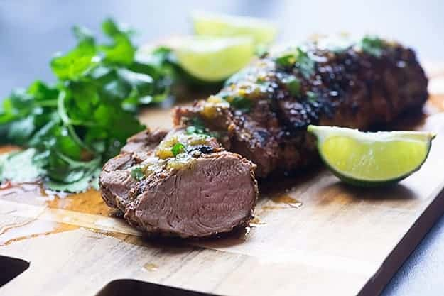 A wooden cutting board with pork tenderloin and lime wedges on it.