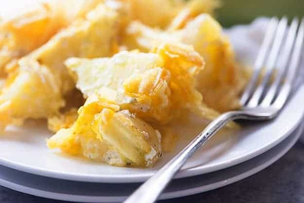 A close up of cheesy potatoes on a white plate.