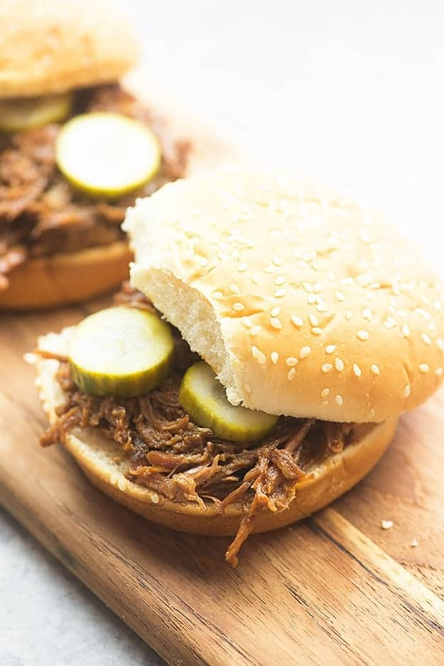 A shredded beef sandwich on a wooden cutting board.