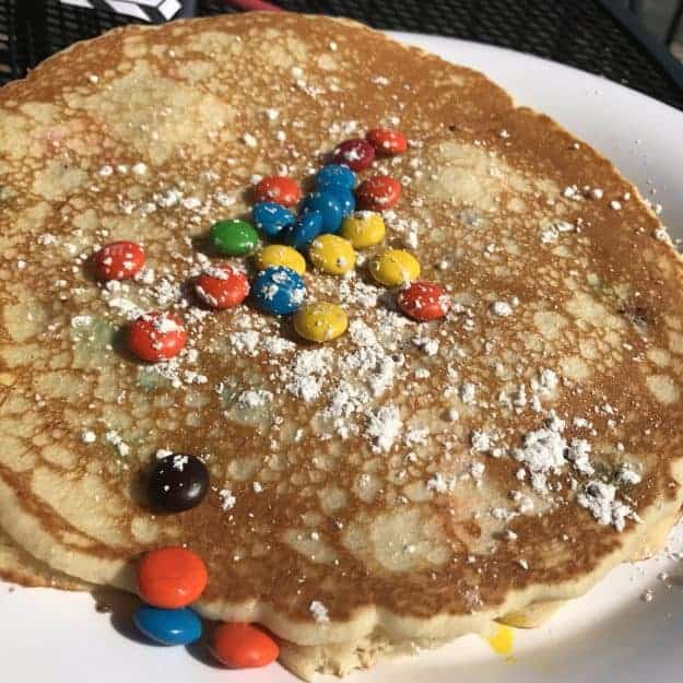Pancakes topped with powdered sugar and m&m\'s