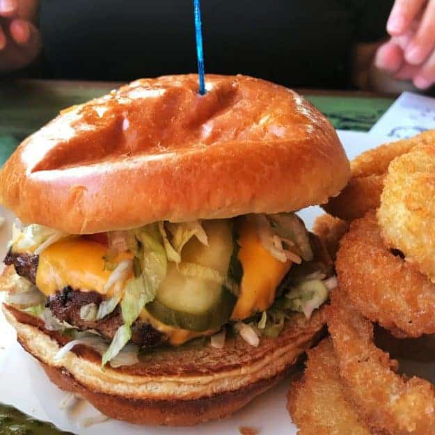 A close up of a sandwich on a plate next to onion rings.