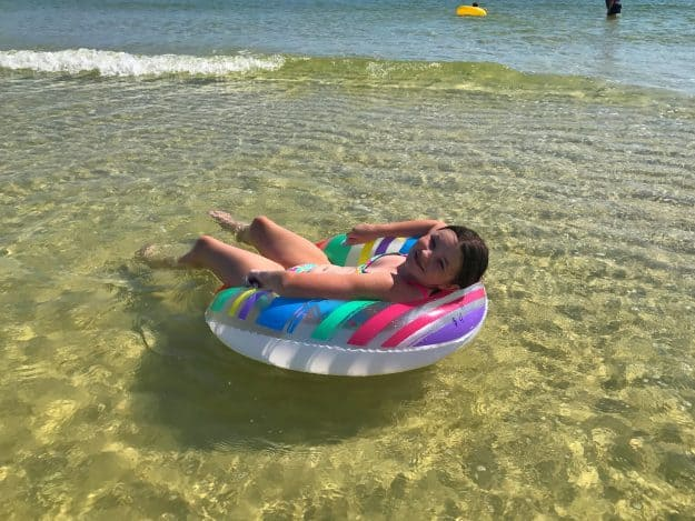 A girl lying on a round float at the beach.
