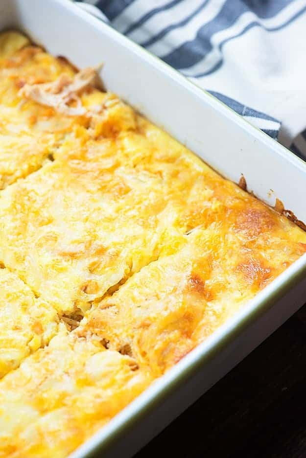 Chicken casserole cut into squares in a white baking pan.