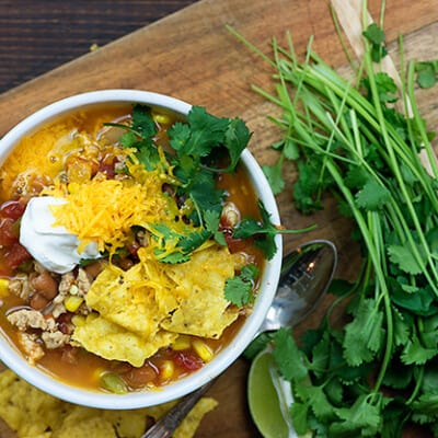A bowl of taco soup on a wooden serving dish