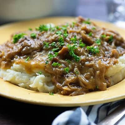 crock pot pork roast on yellow plate with gravy