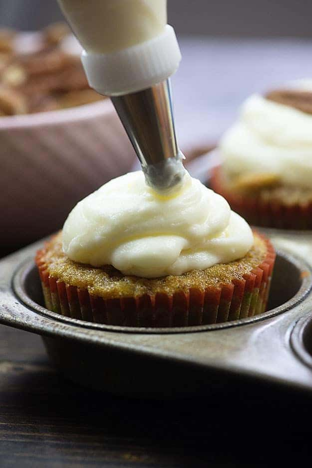 frosting a cupcake in muffin tin